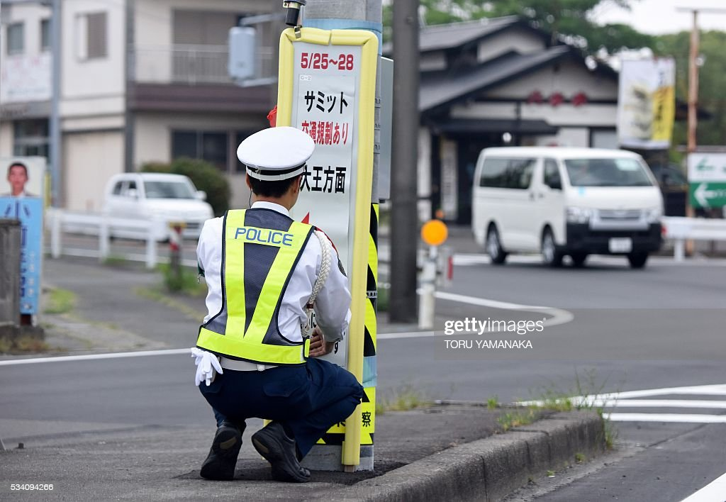 A policeman stands by a sign board showing traffic regulations due to the Group of Seven (G7) summit meeting in Shima, Mie prefecture, on May 25, 2016. Japan is on high-alert ahead of a Group of Seven summit with thousands of police on the streets of Tokyo and fanning out across the country as authorities boost security to unprecedented levels. / AFP / TORU