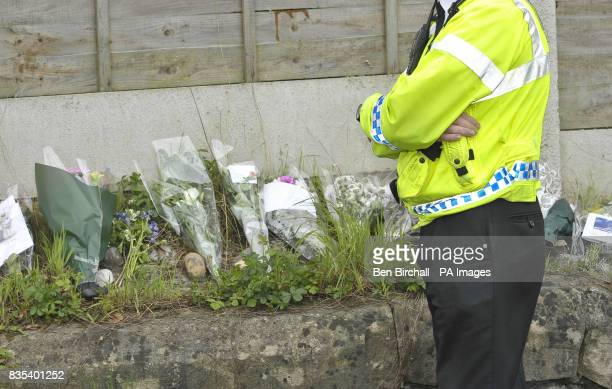 A policeman stands by floral tributes on a wall near the pavement where 11yearold Sam Riddall died after a car ploughed into him and his friends on...