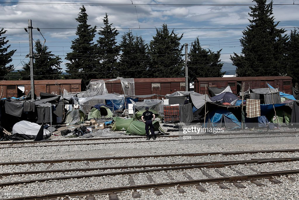 A policeman stands by tents during a police operation at a refugee and migrant camp along the border between Greece and Macedonia, near the village of Idomeni, northern Greece on May 25, 2016. Greek police restarted an operation to move migrants out of Idomeni, the squalid tent city where thousands fleeing war and poverty have lived for months. The migrants and refugees on May 24 were bussed to newly opened camps near Greece's second city Thessaloniki, about 80 kilometres (50 miles) to the south. / AFP / POOL / STR