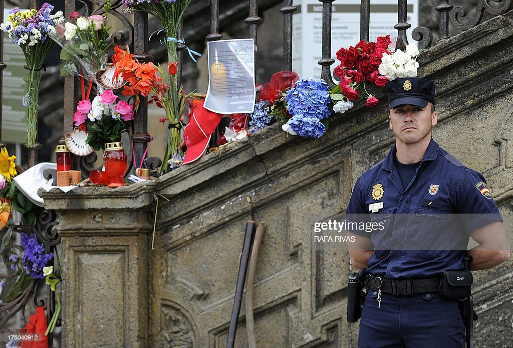 A policeman stands close to flowers and candles displayed at the Obradoiro Square during a memorial service for the victims the derailed train of Angrois, at the cathedral of Santiago de Compostela on July 29, 2013. The driver of a train that hurtled off the rails in Spain was charged on July 28 with 79 counts of reckless homicide and released on bail after being questioned by a judge.