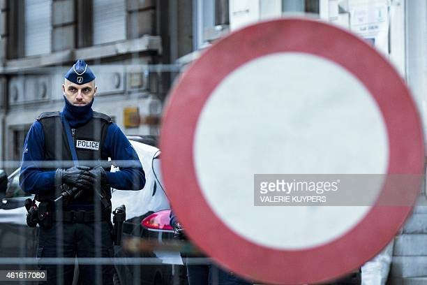 A policeman stands guard at Colline street in Verviers eastern Belgium on January 16 after police shot dead two suspects in a gun battle after they...