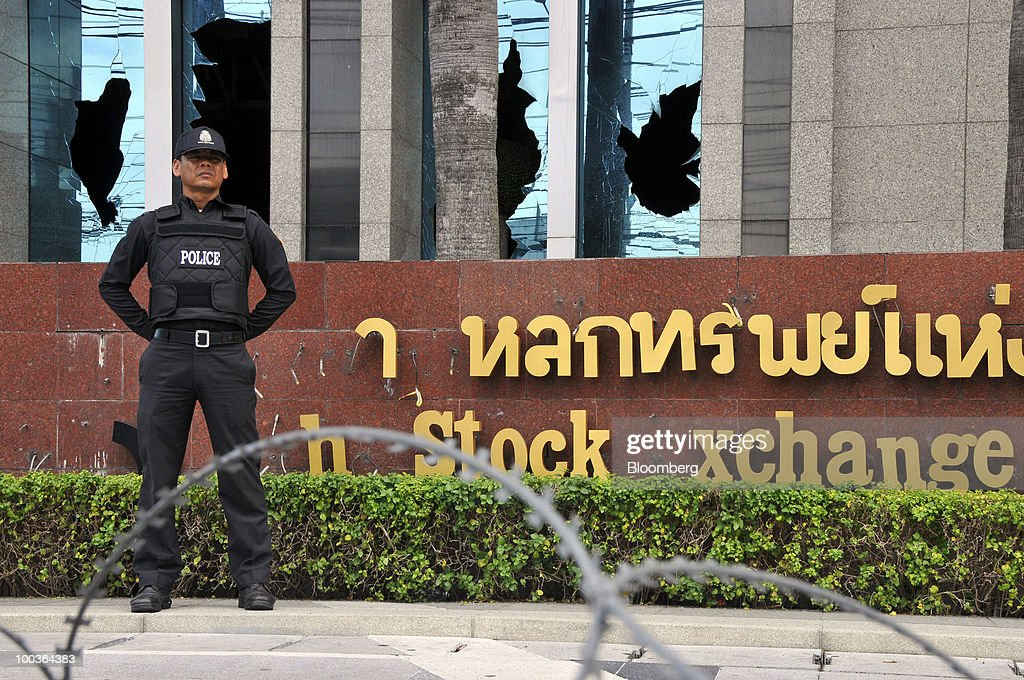 A policeman stands guard behind barbed wire, in front of the broken windows of the Stock Exchange of Thailand (SET), in Bangkok, Thailand, on Monday, May 24, 2010. The Stock Exchange of Thailand returned to normal trading hours of between 10 a.m. and 4:30 p.m. today after cutting short trading hours between May 17 and 19 and shutting the market on May 20 and 21 on political unrest. Photographer: Udo Weitz/Bloomberg via Getty Images