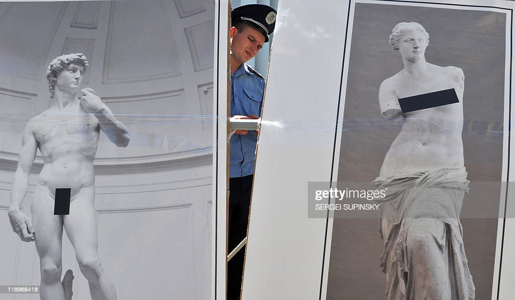 A policeman stands guard behind placards depicting 'censored' masterpieces of world art during auction in front of Ukraine's President Viktor...