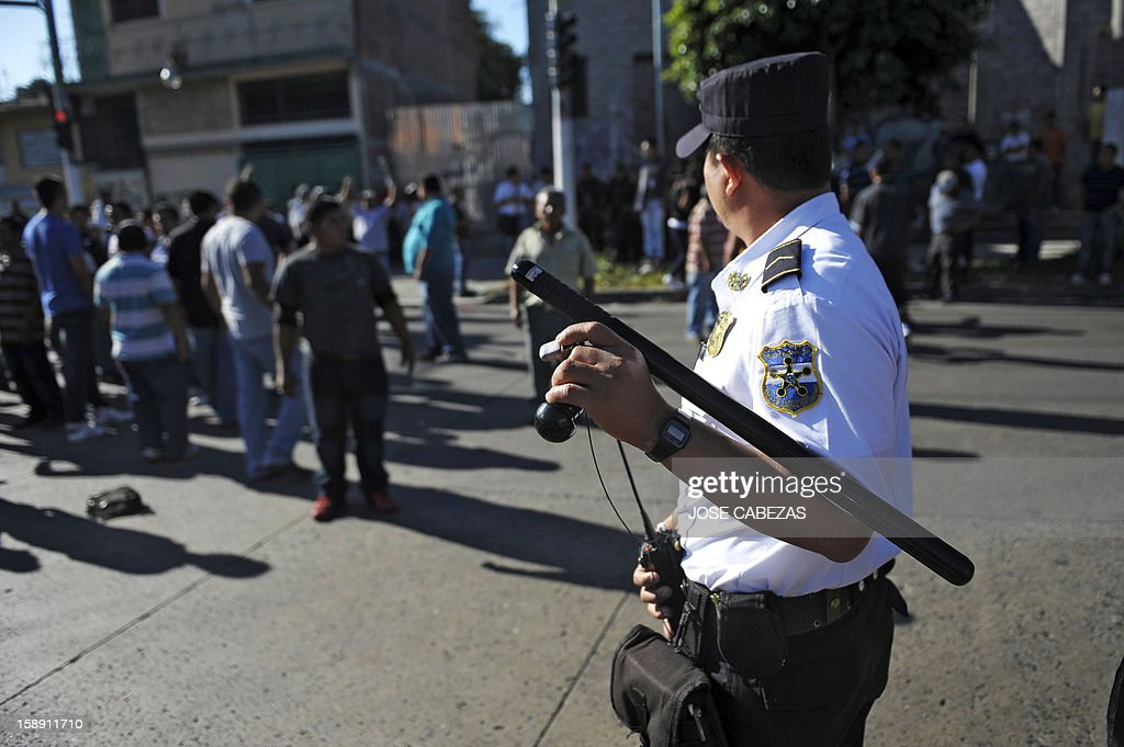 A policeman stands guard during a protest of bus drivers in San Salvador, on January 3, 2013. Bus owners and drivers called for a strike in demand of a rise in the price of the ticket for the buses of public transportation. AFP PHOTO/ Jose CABEZAS