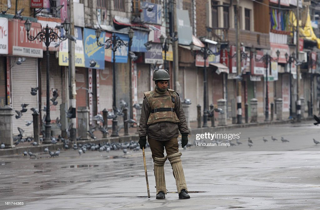 Policeman stands guard during curfew in entire valley to thwart the 'Eid-Gah challo' call given by separatist's parties on February 15, 2013 in Srinagar, India. Most of the valley is reeling under strict curfew and all roads coming to summer capital has been blocked with concertina wires and road blockades.
