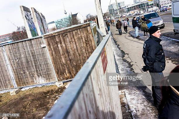 A policeman stands guard in front of a section of the Berlin Wall which has been removed to make way for a luxury apartments development on March 27...