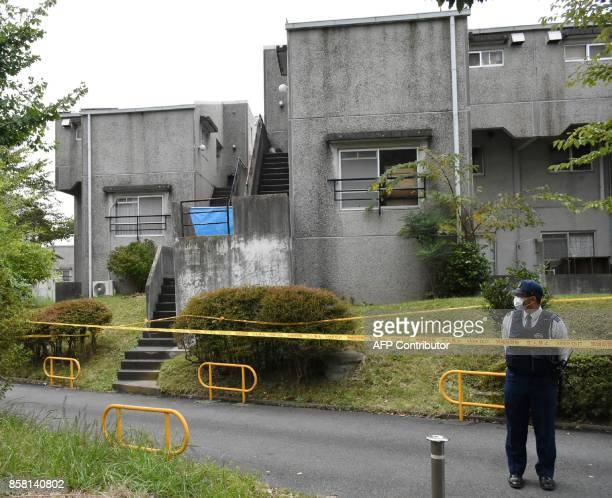 A policeman stands guard in front of an apartment where six members of a family died in Hitachi City on October 6 2017 A 32yearold Japanese man was...
