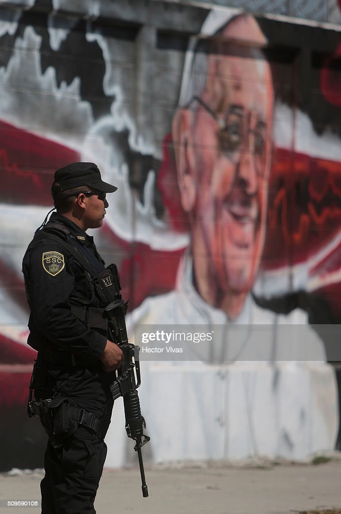 A policeman stands guard near a graffiti painted to welcome Pope Francis near the esplanade where Pope Francis will give a mass for 300 thousand people during the preparations ahead the visit of Pope Francis to Mexico at Las Americas on February 11, 2016 in Ecatepec, Mexico.