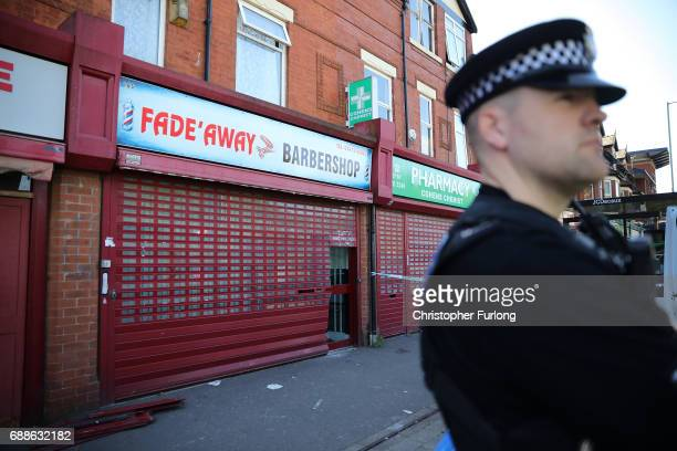 A policeman stands guard next to a barbers shop on Princess Road Moss Side after being raided by antiterror police during the investigation of the...
