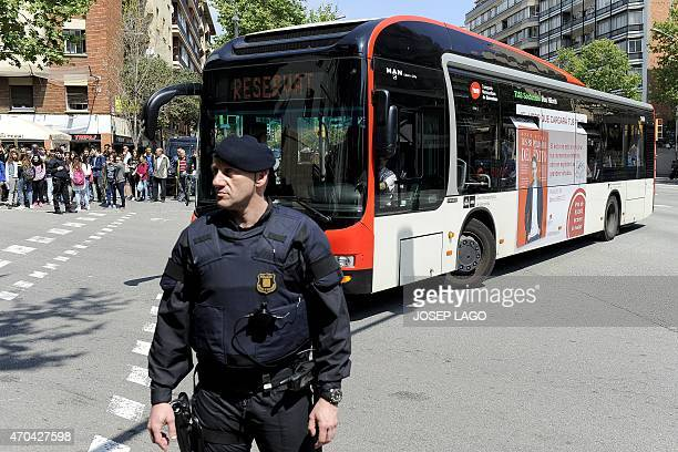 A policeman stands guard next to a bus carrying students of the Joan Fuster Institute in a bus in Barcelona on April 20 2015 after a student...