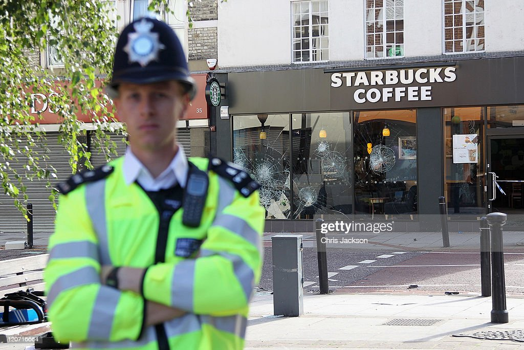 A policeman stands guard outside Starbucks on St John's Road after last night's rioting at Clapham Junction on August 9 2011 in London England...