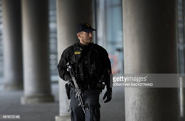 A policeman stands guard outside terminal 3 at Kastrup airport in Copenhagen on November 18 2015 Danish police evacuated one of two terminals at...