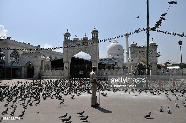 A policeman stands guard outside the shrine of Hazratbal shrine during curfew on August 5 2016 in Srinagar India More than 50 people have been killed...
