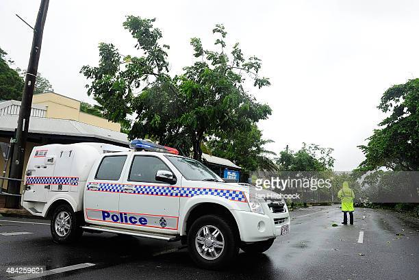 A policeman stands guard to keep onlookers away from fallen powerlines laying across a street on April 12 2014 in Port Douglas Australia The cyclone...