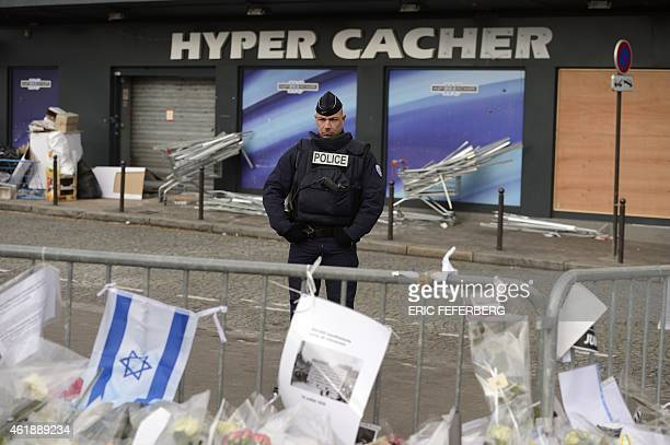 A policeman stands guards on January 21 2015 in front the Hyper Cacher kosher supermarket where jihadist gunman Amedy Coulibaly killed four people on...