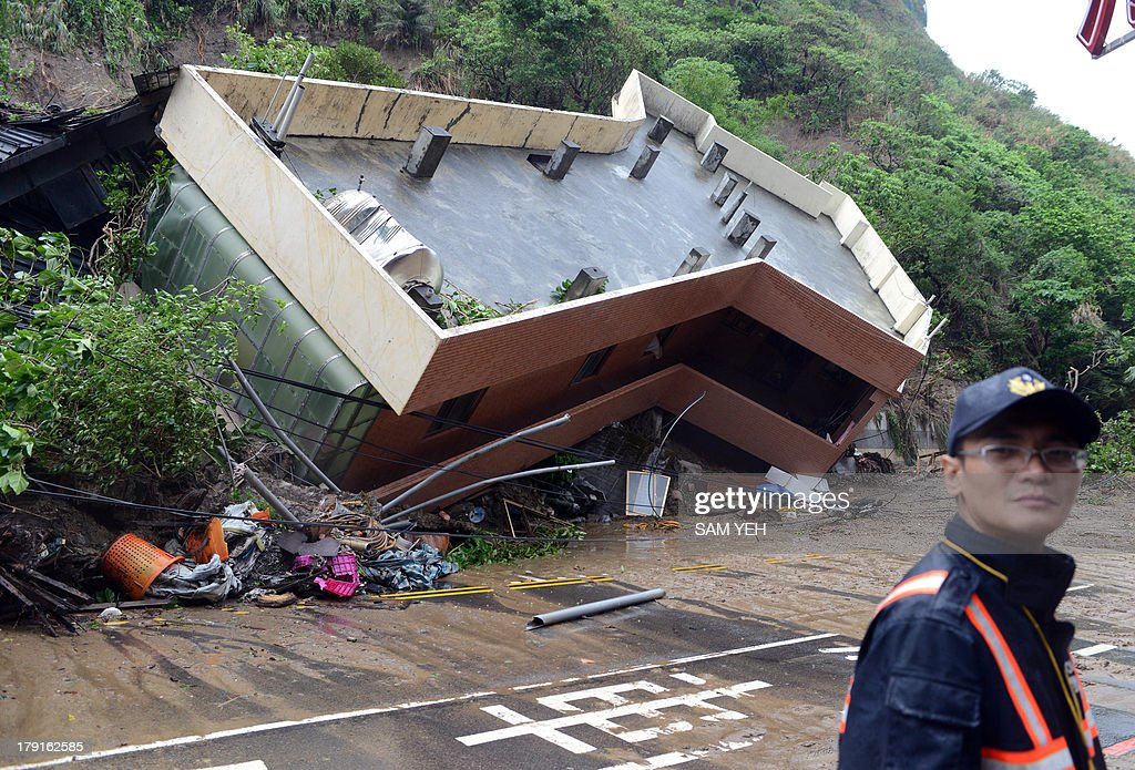 A policeman stands in front of a building damaged after heavy rains hit Taiwan's northern city of Keelung on September 1, 2013. Tropical Storm Kong-Rey pounded Taiwan, leading to widespread flooding in the south that left three people dead and caused more than 11 million USD in agricultural damage, the government said. AFP PHOTO / Sam Yeh