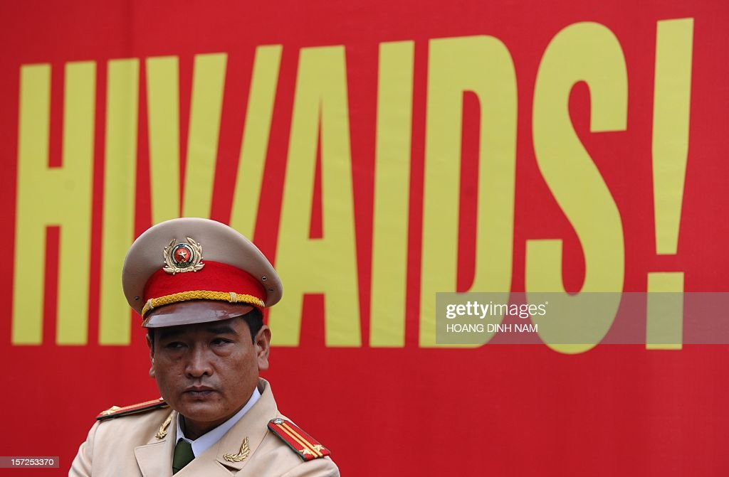 A policeman stands in front of a large HIV/Aids poster during a meeting in Hanoi on December 1, 2012. Since the first HIV case detected in 1990, the number of cases is projected to be 280,000 or 0.47 percent of the Vietnamese population in 2012 with injecting drug users (IDU) accounting for up to 65 percent of people living with HIV. AFP PHOTO / HOANG DINH Nam / AFP / HOANG