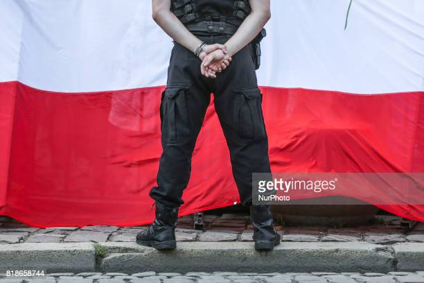 A policeman stands in front of a national flag during another day of protests against government plans for sweeping changes to Polands judicial...