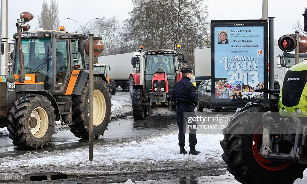 A policeman stands in front of the partial blockade organized by farmers with some hundred tractors during a demonstration called by farmers local union FDSEA in Arras, northern france, on January 15, 2013. They denounce all kinds of pressure affecting their activities. The municipalty board at right reads : 'Best wishes'.