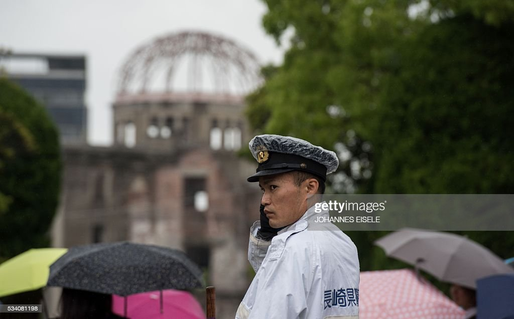 A policeman stands in front of the Peace Memorial Genbaku Dome in the Hiroshima Peace Memorial park in Naka Ward, Hiroshima Prefecture on May 25, 2016. Barack Obama is set to become the first sitting US president to visit Hiroshima when he journeys on May 27 with Japanese Prime Minister Shinzo Abe, hallowed ground to Japanese but, for more than 70 years, a no-go zone for 11 of his Oval Office predecessors. / AFP / JOHANNES