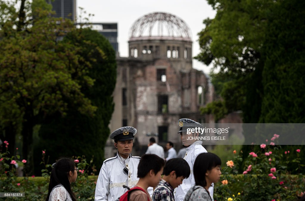 Policeman stands in front of the Peace Memorial Genbaku Dome in the Hiroshima Peace Memorial park in Naka Ward, Hiroshima Prefecture on May 25, 2016. US President Barack Obama is set to become the first sitting US president to visit Hiroshima when he journeys on May 27 with Japanese Prime Minister Shinzo Abe, hallowed ground to Japanese but, for more than 70 years, a no-go zone for 11 of his Oval Office predecessors. / AFP / JOHANNES