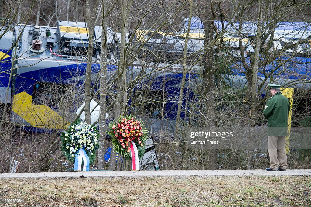 A policeman stands in front of two chaplets near the wreckage of two trains that collided head-on the day before in Bavaria on February 10, 2016 near Bad Aibling, Germany. Authorities say at least nine people are dead and over 100 injured in the collision between two trains of the Meridian local commuter train service that occurred at approximately 7:00 am yesterday.