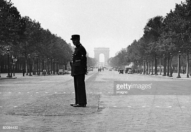 A policeman stands lonely on the Champs Elysee The most Parisians leave the city in AugustParis France Photograph Around 1930 [Ein Polizist steht...