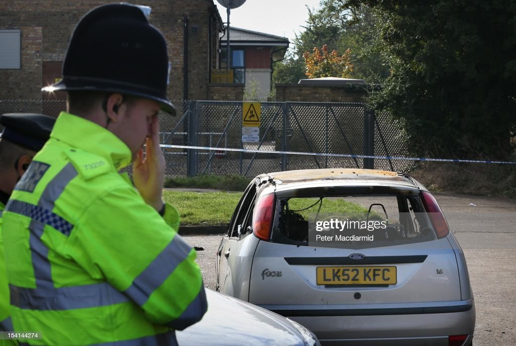 A policeman stands near the remains of a burnt out car near a house fire on October 15, 2012 in Harlow, England. A woman and three children have died and another three are in hospital after a fire in a house on an estate near Harlow in Essex.