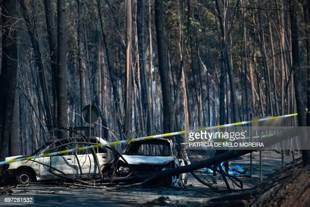 A policeman stands near two burnt cars and the dead body of a victim of a wildfire in a forest of Figueiro dos Vinhos on June 18 2017 A wildfire in...