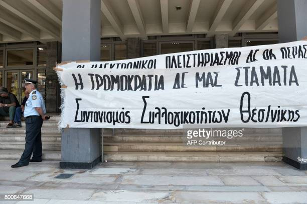 A policeman stands next to a banner reading 'Auctions online won't pass Terrorism does not stop us' outside of the courthouse as demonstrators...