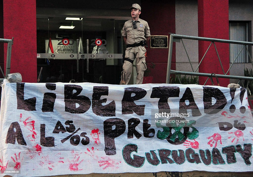 A policeman stands next to a banner reading 'Freedom for the prisoners of Curuguaty' during a vigil of supporters of ousted Paraguayan President Fernando Lugo and relatives of jailed peasants on November 21, 2012 in Asuncion. Four peasants accused -alongside other eight people- of the death of six policemen past June 15 in Curuguaty, 250 km northeast of Asuncion, remain on hunger strike. 11 peasants died in the confrontation with the police during the eviction of a private property. AFP PHOTO/ Norberto Duarte
