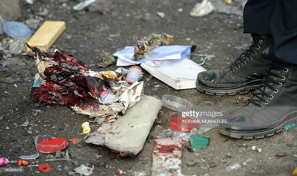 A policeman stands next to a blood stained newspaper at one of the blast sites at Dilsukh Nagar in Hyderabad on February 22, 2013 the morning after twin bomb attacks killed 14 people and wounded dozens more. The bombings, the first to hit India since 2011, hit a mainly Hindu district in Hyderabad, a hub of India's computing industry which hosts local offices of Google and Microsoft among others and which has a large Muslim population. AFP PHOTO / Indranil MUKHERJEE