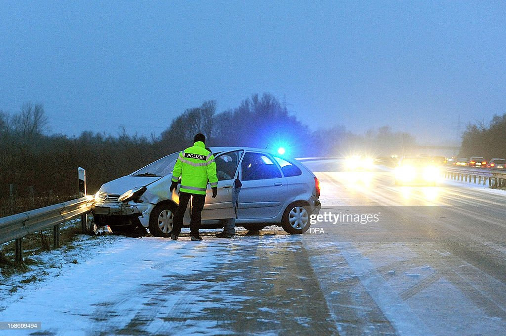 A policeman stands next to a crashed car on a motor- way near Schleswig, northern Germany on December 22, 2012. Temperatures around the freezing point led to icy conditions in northern and eastern parts of Germany. AFP PHOTO / Karsten Sörensen GERMANY OUT