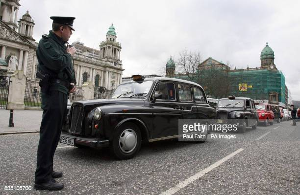 A Policeman stands next to a line of taxi cabs whose drivers are protesting in Belfast city centre over the lack of taxi ranks
