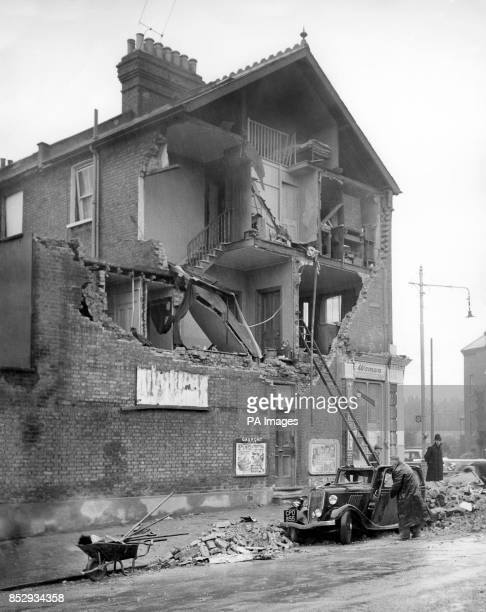 A policeman stands on duty as the work of clearing up the rubble continues outside an Acton house that was badly damaged by the whirlwind In the road...