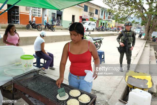 A policeman stands on guard behind a female street vendor making Arepas in the first Christmas after signing of the peace treaty between Farc...
