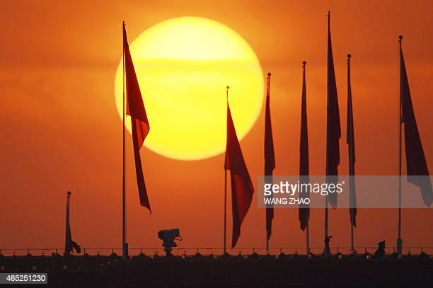 A policeman stands on the top of the Chinese National Museum over looking Tiananmen square before the opening session of the National People's...