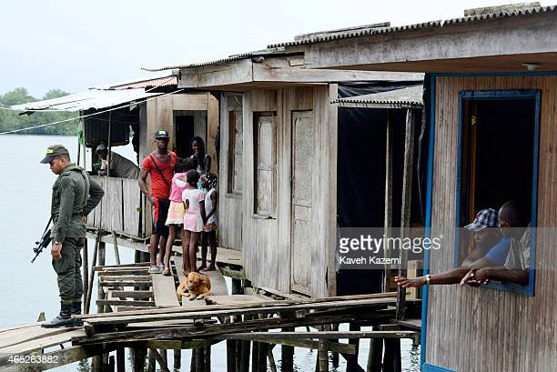 BUENAVENTURA COLOMBIA JANUARY 14 2015 A policeman stands on the wooden plank walkway keeping an eye on the sea front while the residents and a dog...