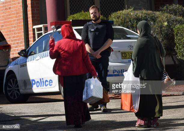 A policeman stands outside a block of flats in the Sydney suburb of Lakemba on August 1 after counterterrorism raids across the city at the weekend...