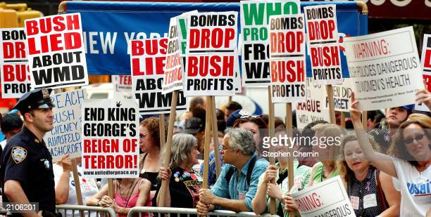 A policeman stands watch as hundreds of activists gather to protest US President George W Bush's policies on women's health the war with Iraq and...