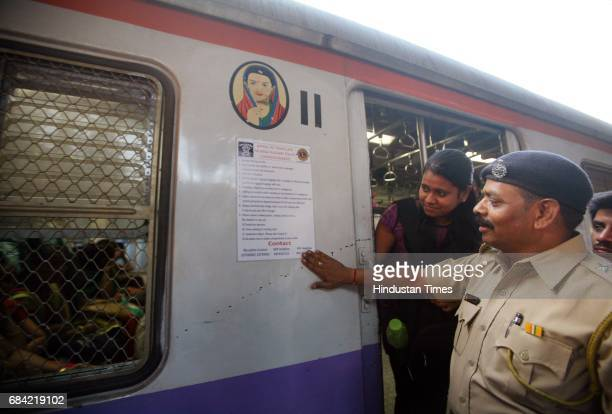 A policeman sticks a poster on saftety tips to women commuters outside the ladies coach of a local train on the first day of the safety week which is...