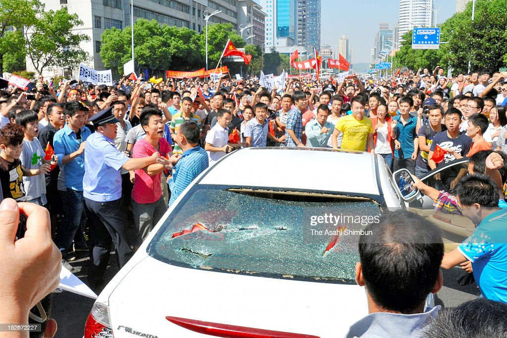A policeman stops a protester shouting to the Japaneses car driver during an anti-Japan rally on September 15, 2012 in Changsha, China. There were protests in many major cities in China, including Shanghai, Shenzhen, Shenyang, Hangzhou, Harbin, Qingdao and Hong Kong as they protest to the Japanese government's purchase of the disputed Senkaku/Diaoyu islands.
