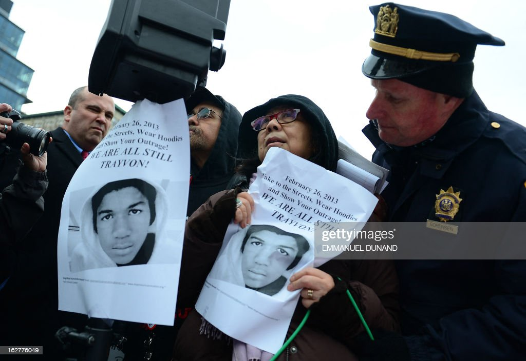A policeman stops demonstrators to use a loudspeaker as they take part in a protest wearing hoodies in New York, February 26, 2013 to mark the one-year anniversary of the fatal shooting in Florida of black teenager Trayvon Martin by neighboorhood watchman George Zimmerman. Zimmerman, a neighborhood watch volunteer who called the police after seeing what he said was a suspicious character in a neighborhood with a history of break-ins, pleaded not guilty to a second-degree murder charge and said he acted in self-defense. AFP PHOTO/EMMANUEL DUNAND