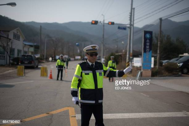 A policeman stops traffic outside a golf course being used as the site for the recently installed US Terminal High Altitude Area Defense system in...