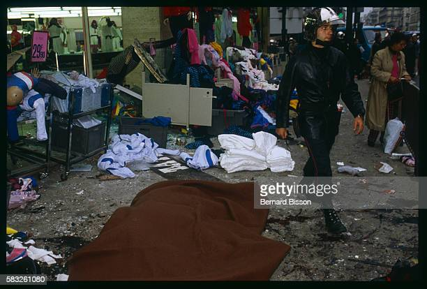 A policeman strides through the clothes and accessories strewn across the pavement outside the entrance of the Tati department store on Rue de Rennes...