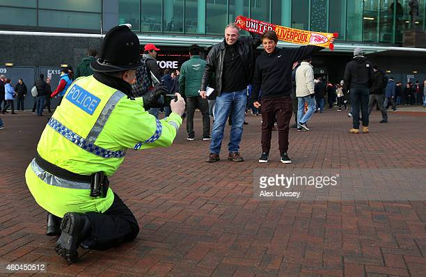 Policeman takes a photo of fans prior to the Barclays Premier League match between Manchester United and Liverpool at Old Trafford on December 14...