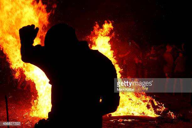 A policeman takes cover as a flammable canister explodes in a large fire burning in the 'Ute Paddock' camp ground on the second day of the 2014 Deni...