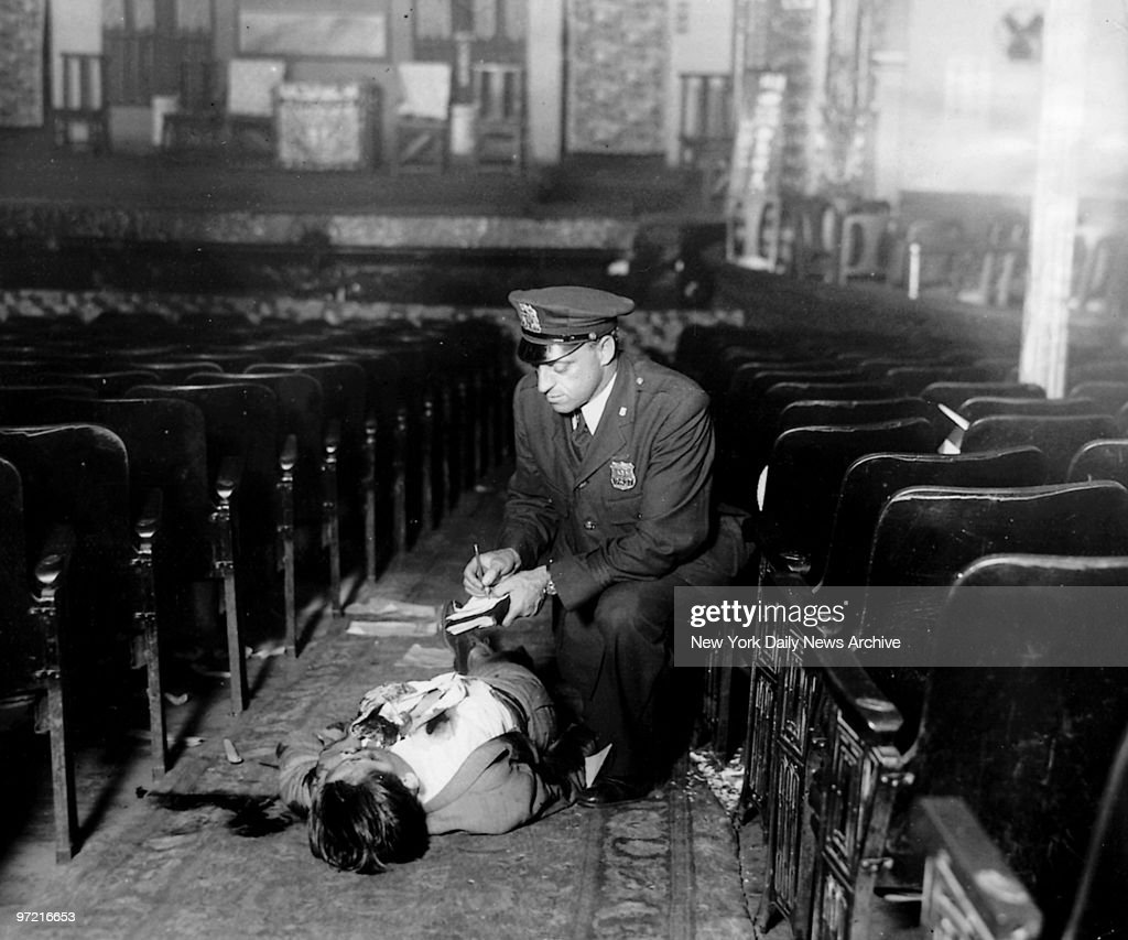 A policeman takes notes over the body of murder victim Hangwah Hung on the floor of the People's Theatre.