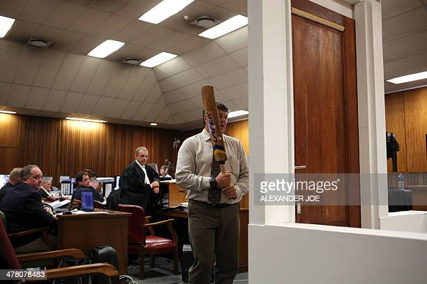 A policeman takes part in the reconstruction of the hitting of the door with the cricket bat during the trial of South African Paralympic athlete...