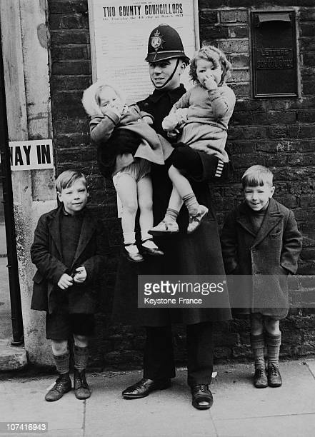 Policeman Taking Care Of Children While Parents Were Voting In England On March 1937